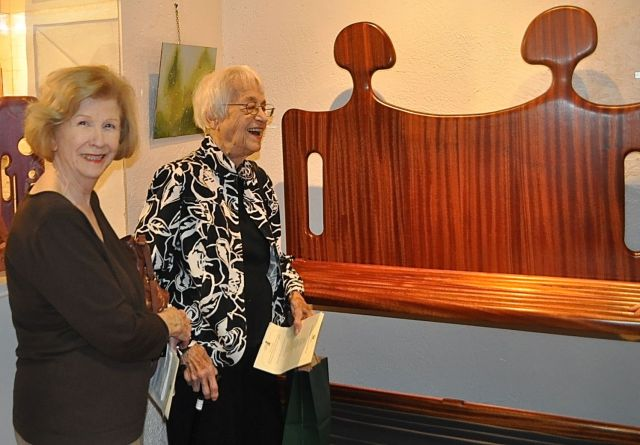 """Guests interacting over """"Conversation Seat"""". Artwork in Mahogany wood."""